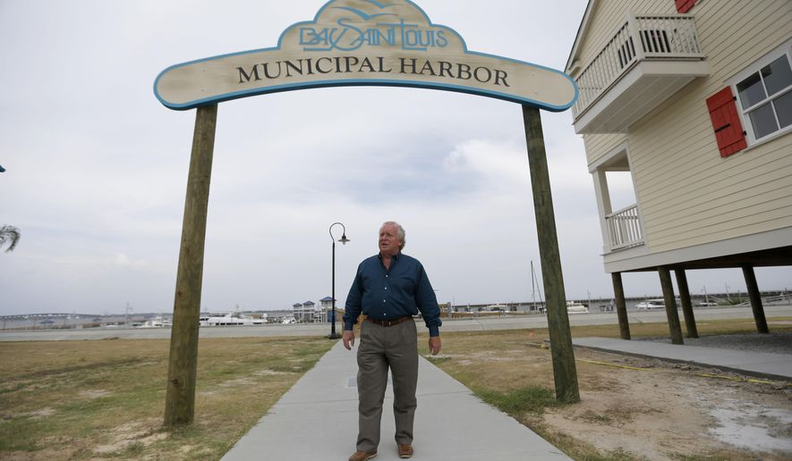 In this Monday, Aug. 25, 2014 photo, Bay St. Louis Mayor Les Fillingame stands for a photograph at the town's new Municipal Harbor in Bay St. Louis, Miss. With the federal money that largely paid for Hurricane Katrina recovery projects drying up, Bay St. Louis is running out of cash and faces a new challenge: Having won a war of recovery, how to survive a return to normal in its aftermath. (AP Photo/Gerald Herbert)