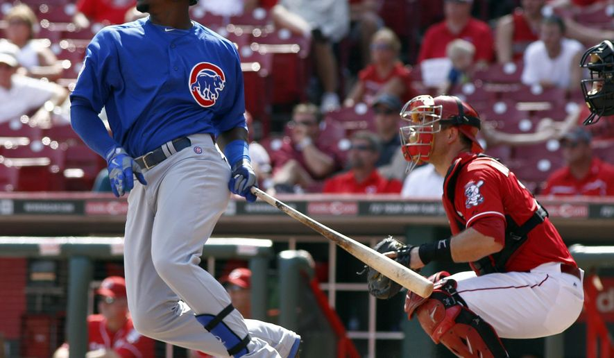 Chicago Cubs' Jorge Soler, left, watches his RBI-single hit off Cincinnati Reds relief pitcher Jumbo Diaz in the ninth inning of a baseball game, Thursday, Aug. 28, 2014, in Cincinnati. Reds catcher Devin Mesoraco, right, looks on. The Reds won 7-2. (AP Photo/David Kohl)