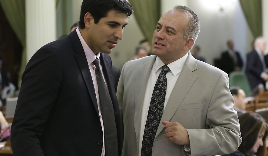 Assemblyman Raul Bocanegra, D-Pacoima, right, discusses a bill with Assemblyman Matt Dababneh, D-Van Nuys at the Capitol in Sacramento, Calif., Thursday, Aug. 28, 2014. By a 54-12 vote, lawmakers approved a bill co-authored by Bocanegra and Assembly Reginald Jones-Sawyer, D-Los Angeles, that would prohibit sports franchise owners like Donald Sterling from writing off fines imposed by sports leagues as business expenses. (AP Photo/Rich Pedroncelli)
