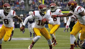 Southern California's Anthony Brown, center, runs in the ball for a touchdown after blocking a punt by Washington's Travis Coons during the first half of an NCAA college football game Saturday, Oct. 13, 2012, in Seattle. (AP Photo/Elaine Thompson)
