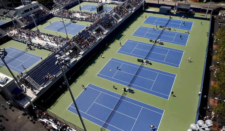 Visitors to the Billie Jean King Tennis Center watch players practice on new practice courts at the U.S. Open tennis tournament, Wednesday, Aug. 27, 2014, in New York. In the first stage of a sweeping renovation of the USTA National  Tennis Center, an elevated row of stands now looms over the practice courts where star players once hit balls, tinkered with strategy and bickered with their coaches in relative privacy. (AP Photo/Matt Rourke)