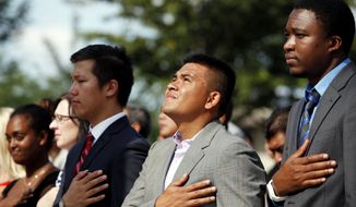 """WASHINGTON, DC - August 28, 2014: Citizenship candidates (from left) Chimed Altandush, of Mongolia, Dennis Pineda, of Honduras, and Eric Mani, of Cameroon, stand for the national anthem during a special naturalization ceremony held at the Dr. Martin Luther King Jr. Memorial in Washington, DC. The ceremony was held at the memorial in commemoration of the 51st anniversary of Dr. Martin Luther King Jr's """"I Have a Dream"""" speech. (Eva Russo/Special to The Washington Times)"""