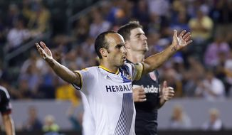 Los Angeles Galaxy's Landon Donovan celebrates after scoring a goal on a penalty kick, next to D.C. United's Bobby Boswell during the second half of an MLS soccer match Wednesday, Aug. 27, 2014, in Carson, Calif. The Galaxy won 4-1. (AP Photo/Danny Moloshok)
