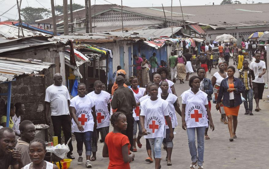 In this photo taken on Wednesday, Aug. 27, 2014,  Red Cross workers walk through a section of West Point, an area that has been hit hard by the Ebola virus, with residents not allowed to leave as government forces clamp down on movement to prevent the spread of Ebola, in  Monrovia, Liberia. The Ebola outbreak in West Africa eventually could exceed 20,000 cases, more than six times as many as are now known, the World Health Organization said Thursday. A new plan released by the U.N. health agency to stop Ebola also assumes that the actual number of cases in many hard-hit areas may be two to four times higher than currently reported. (AP Photo/Abbas Dulleh)