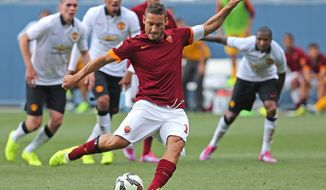 """FILE - In this July 26, 2014 file photo, AS Roma's Francesco Totti kicks for a goal during an exhibition soccer match against Manchester United at Mile High Stadium in Denver, Co. For Italian football fans, merely mentioning the word """"scudetto"""" _ league title _ in association with a favorite club is considered tabu. The theory goes that it's better left unsaid until your squad actually raises the trophy. Yet recently, the word has begun popping up in animated discussions inside Rome's myriad coffee bars and impassioned sports-talk radio stations. The talk, and not only in the capital, is that Roma can put together a serious challenge for the Serie A title this season. Three years after takeover by US owners, Roma is expected to contend for the Serie A title. (AP Photo/Brennan Linsley, file)"""