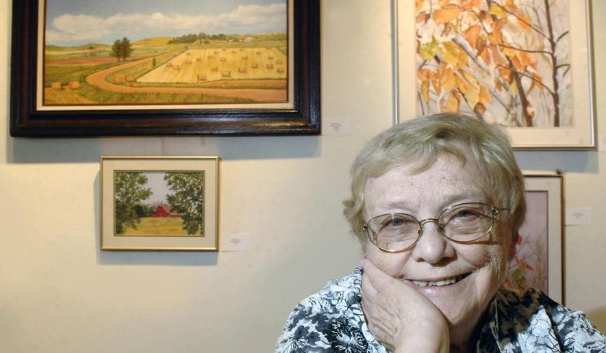 ADVANCE FOR RELEASE MONDAY, SEPT. 1, 2014, AND THEREAFTER - In this Aug. 5, 2014 photo, New Salem/Almont artist Audrey Bauer poses with some of her work that captures the North Dakota farmland and prairie landscape through watercolor and oil paintings. (AP/Bismarck Tribune, Mike McCleary)