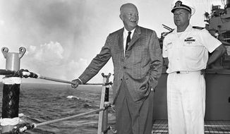 President Dwight Eisenhower stands with Capt. John A. Maurer, skipper of the cruiser St. Paul, as the warship moves along the Southern tip of Formosa during trip from Manila. (AP Photo, file)