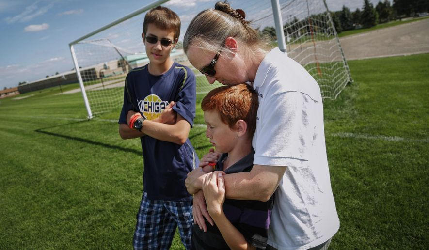 In this Wednesday, Aug. 27, 2014 photo, Kris Bieniewicz, of Westland, and her sons Josh Bieniewicz, 9, and Kyle Bieniewicz, 14, remember her husband and their father, John Bieniewicz, at the soccer fields of Founders Sports Park in Farmington Hills, where the boys have played soccer and their father officiated matches. John Bieniewicz died earlier this summer after being punched while refereeing during a soccer game in Livonia, Mich. (AP Photo/Detroit Free Press, Ryan Garza) DETROIT NEWS OUT;  NO SALES