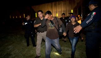 Immigration officials detain Central American migrants during a raid by federal police on a northbound freight train, in San Ramon, Mexico, just after midnight on Friday, Aug. 29, 2014. Migrants captured in raids are deported to their home countries. The largest crackdown by Mexican authorities on illegal migration in decades has decreased the flow of Central American migrants trying to reach the United States, and has dramatically cut the number of child migrants and families, according to officials and eyewitness accounts along the perilous route.(AP Photo/Rebecca Blackwell)