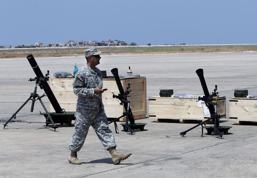 A U.S. soldier walks past mortars at the Rafik Hariri International Airport in Beirut, Lebanon, Friday, Aug. 29, 2014. The United States has delivered the first shipment of weapons to Lebanon to help bolster its military as it faces a growing threat from Islamic militants amid the fallout from neighboring Syria's civil war. (AP Photo/Bilal Hussein)