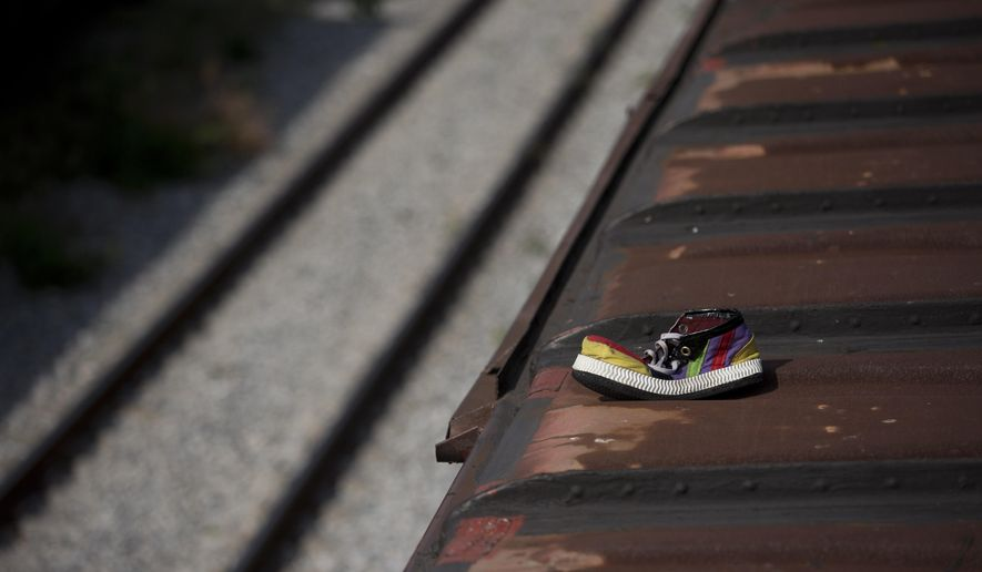 In this Aug. 27, 2014 photo, a sole clown shoe belonging to Honduran migrant Jorge Ruiz Williams, 20, lies atop a freight train after it arrived at the station in Ixtepec, Mexico. Migrants who had been riding atop the train from Arriaga to Ixtepec reported that authorities staged a raid on the train in the middle of the night, arresting many migrants and sending others fleeing into the darkness. Ruiz Williams was one of the lucky handful who was able to escape the police and re-board the train. Seen later in a migrant shelter in Ixtepec, he said he had lost both shoes, but the rest of his professional clown costume was intact. (AP Photo/Rebecca Blackwell)