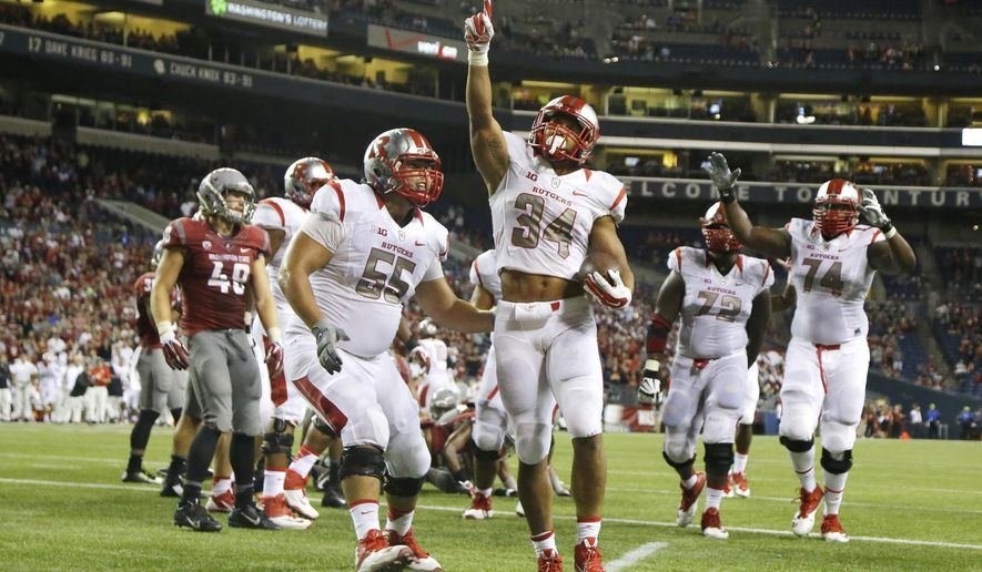 Rutgers running back Paul James (34) points upward after he rushed for a touchdown in the second half of an NCAA college football game against Washington State, Thursday, Aug. 28, 2014, in Seattle. Rutgers beat Washington State 41-38.  (AP Photo/Ted S. Warren)