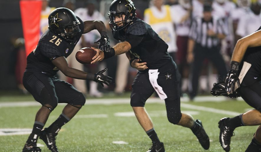 Vanderbilt quarterback Patton Robinette, right, hands off the ball to running back Ralph Webb (26) in the first quarter of an NCAA college football game against Temple on Thursday, Aug. 28, 2014, in Nashville, Tenn. (AP Photo/Brian Powers)