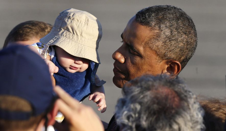 President Obama holds up four-month-old Ryan Kelley, of Richmond, R.I., while greeting a gathering shortly after arriving at T.F. Green Airport in Warwick, R.I., Friday, Aug. 29, 2014. The president traveled to Rhode Island to attend a Democratic fundraiser in Newport on Friday. (AP Photo/Charles Krupa)