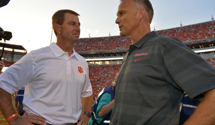 FILE - In this Aug. 31, 2013, file photo, Clemson's coach Dabo Swinney, left, greets Georgia's head coach Mark Richt before the start of an NCAA college football game at Memorial Stadium in Clemson, S.C. Swinney believes his players can absorb the late losses of running back Zac Brooks to a foot injury and offensive lineman Shaq Anthony deciding to transfer for more playing time. The 16th-ranked Tigers don't have much choice since they open at No. 12 Georgia on Saturday. (AP Photo/ Richard Shiro, File)