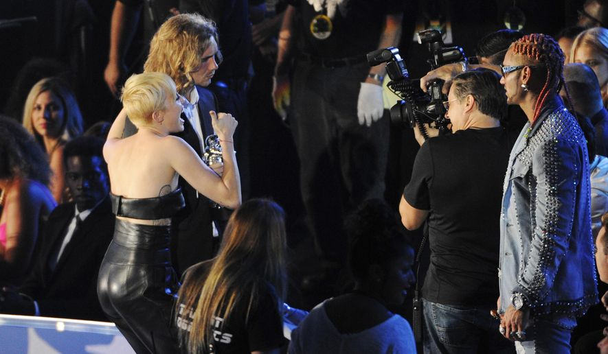 FILE - In this Sunday, Aug. 24, 2014 file photo, Miley Cyrus, left, stands with Jesse Helt holding her award at the MTV Video Music Awards at The Forum in Inglewood, Calif. The young homeless man who accompanied Miley Cyrus to the MTV Video Music Awards and who had been sought on an Oregon arrest warrant has turned himself in and posted bail, an Oregon official said Thursday night Aug. 28, 2014. (Photo by Chris Pizzello/Invision/AP, file)