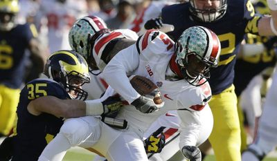 OHIO STATE VS MICHIGAN - Ohio State quarterback Braxton Miller (5) is tackled by Michigan linebacker Joe Bolden (35) during the first quarter of an NCAA college football game in Ann Arbor, Mich., Saturday, Nov. 30, 2013. (AP Photo/Carlos Osorio)