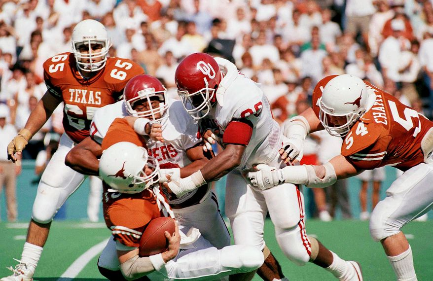 TEXAS VS OKLAHOMA - Unversity of Texas quarterback Bret Stafford is dropped for a loss by Oklahoma University defensive end Darrell Reed, left, and defensive end Troy Johnson, right, during second period of play at the Cotton Bowl, Saturday,October 10, 1987. (AP Photo/Melissa Mehan)