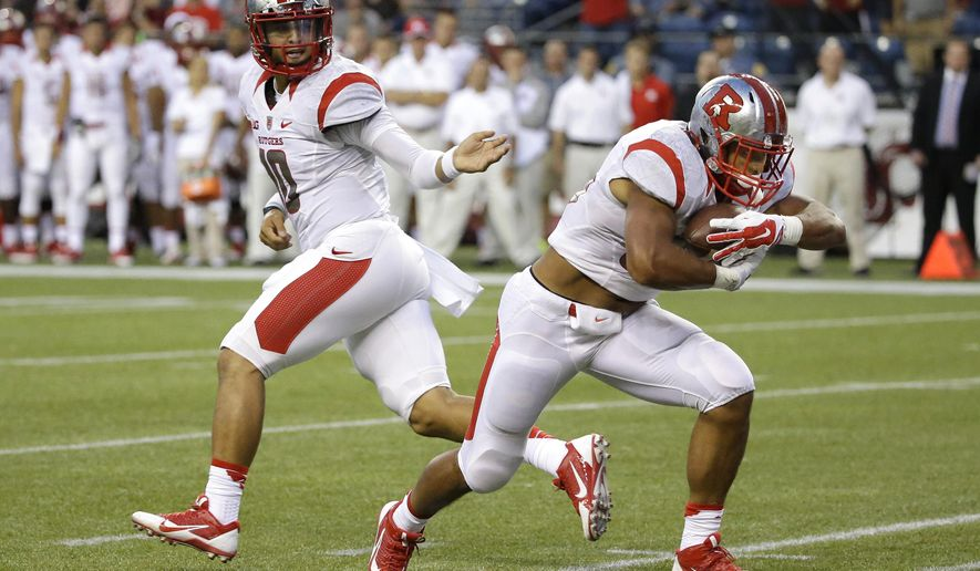 Rutgers quarterback Gary Nova, left, hands off to running back Paul James, who powered through the line for a touchdown against Washington State in the first half of an NCAA college football game, Thursday, Aug. 28, 2014, in Seattle. (AP Photo/Ted S. Warren)