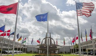 Flags of member nations flap in the wind outside NATO headquarters in Brussels on Friday, Aug. 29, 2014. NATO on Friday urged Russia to cease its military actions and take immediate and verifiable steps towards de-escalation of the crisis in Ukraine. (AP Photo/Olivier Matthys)
