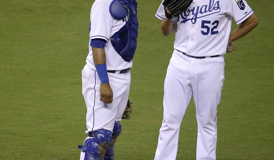 Kansas City Royals pitcher Bruce Chen and catcher Salvador Perez meet on the mound after Perez gave up a pair of runs during the 10th inning of a baseball game against the Minnesota Twins on Thursday, Aug. 28, 2014, in Kansas City, Mo. The Twins won 11-5. (AP Photo/Charlie Riedel)