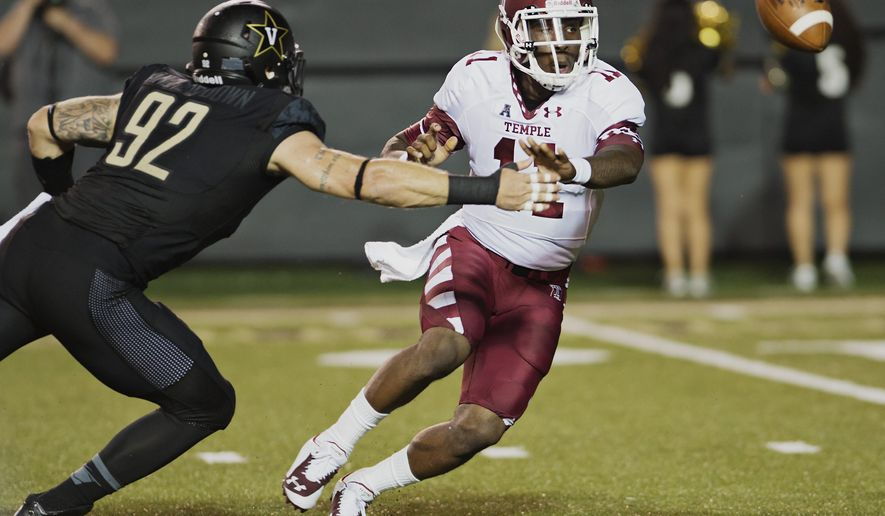 Temple quarterback P.J. Walker (11) tosses the ball before getting hit by Vanderbilt's Kyle Woestmann (92) in the first quarter of an NCAA college football game Thursday, Aug. 28, 2014, in Nashville, Tenn. (AP Photo/Brian Powers)