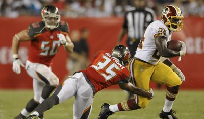 Washington Redskins Silas Redd (24) elludes Tampa Bay Buccaneers defenders Dane Fletcher (50) and Marc Anthony (35) during a NFL preseason football game Thursday, Aug. 28, 2014 in Tampa, Fla. (AP Photo/Steve Nesius)