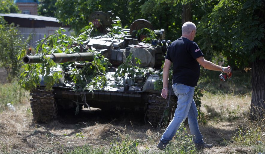 A local resident passes by camouflaged pro-Russian tank in the town of Novoazovsk, in eastern Ukraine, Friday, Aug. 29, 2014. In Novoazovsk, pro Russian rebel fighters looked to be in firm control, well-equipped and relaxed. At least half a dozen tanks were seen on roads around the town, although the total number at the rebels' disposal is believed to be much greater. Novoazovsk fell swiftly to the rebels Wednesday after being pounded by shelling.(AP Photo/Sergei Grits)