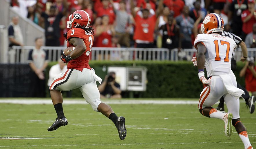 Georgia's Todd Gurley, left, breaks away from Clemson's Kyrin Priester to return a kick-off for a touchdown in the first half of an NCAA college football game, Saturday, Aug. 30, 2014, in Athens, Ga. (AP Photo/David Goldman)