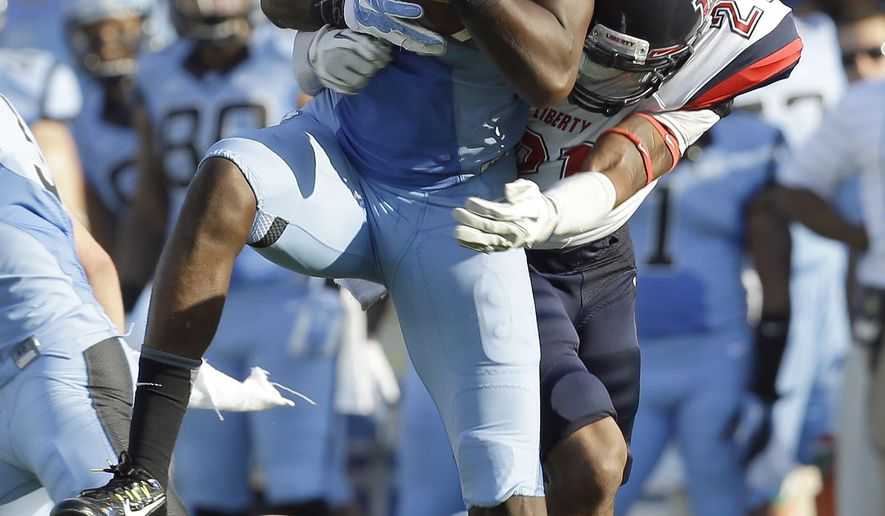 North Carolina's Quinshad Davis (14) catches a pass as Liberty's Wesley Scott (21) defends during the first half of an NCAA college football game in Chapel Hill, N.C., Saturday, Aug. 30, 2014. (AP Photo/Gerry Broome)