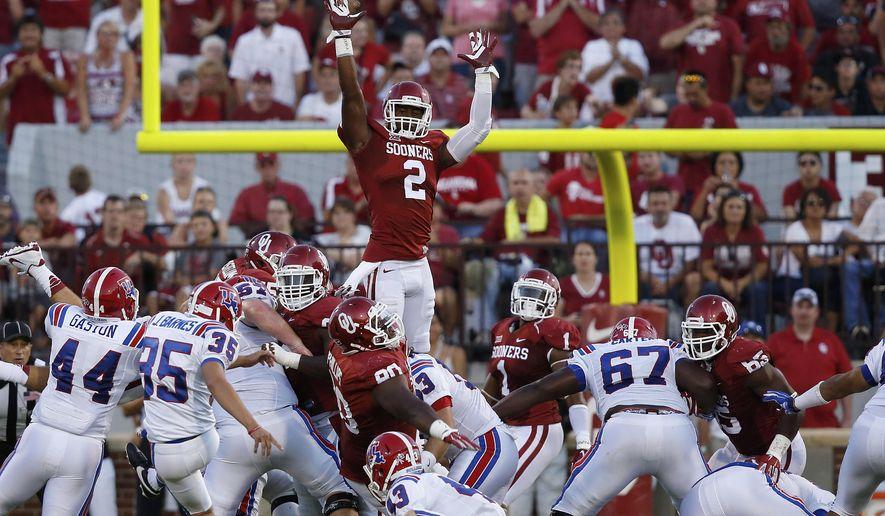 Louisiana Tech's Jonathan Barnes (35) kicks a field goal over Oklahoma's Julian Wilson (2) and the rest of the Oklahoma team in the second quarter of an NCAA college football game in Norman, Okla., Saturday, Aug. 30, 2014. (AP Photo/Sue Ogrocki)