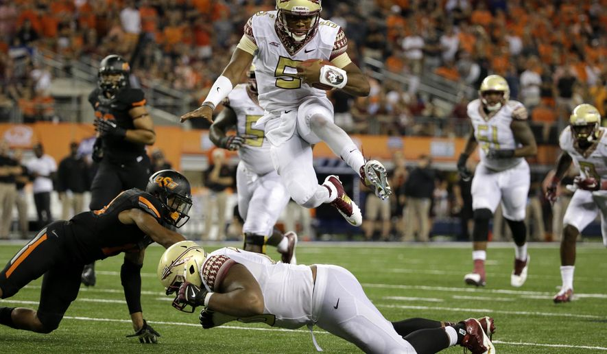 Florida State quarterback Jameis Winston (5) leaps over guard Josue Matias as Oklahoma State safety Jordan Sterns, left, is unable to stop Winston from reaching the end zone for a touchdown in the second half of an NCAA college football game, Saturday, Aug. 30, 2014, in Arlington, Texas. (AP Photo/Tony Gutierrez)