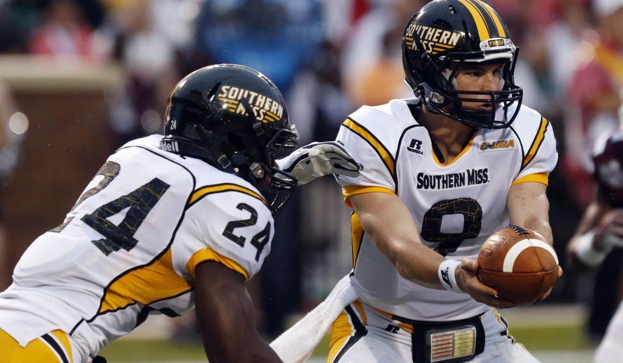 Southern Mississippi quarterback Nick Mullens (9) hands off to running back George Payne (24) in the first quarter of an NCAA college football game against Mississippi State at Davis Wade Stadium in Starkville, Miss., Saturday, Aug. 30, 2014. (AP Photo/Rogelio V. Solis)