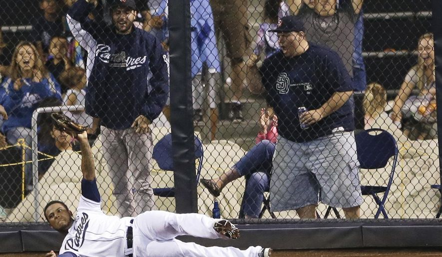 San Diego Padres right fielder Rymer Liriano holds up the ball in his glove after making a leaping catch at the wall for the out on Los Angeles Dodgers' Dee Gordon during the fifth inning in a baseball game Friday, Aug. 29, 2014, in San Diego. (AP Photo/Gregory Bull)