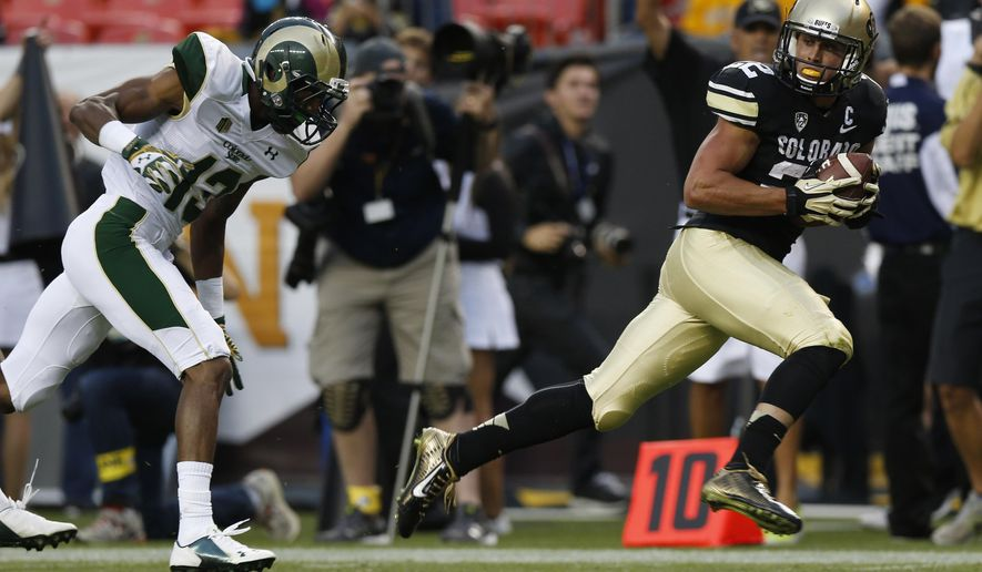 Colorado wide receiver Nelson Spruce, right, runs for the goal line after pulling in a pass for a 54-yard touchdown, in front of Colorado State defensive back DeAndre Elliott in the first quarter of an NCAA college football game in Denver on Friday, Aug. 29, 2014. (AP Photo/David Zalubowski)