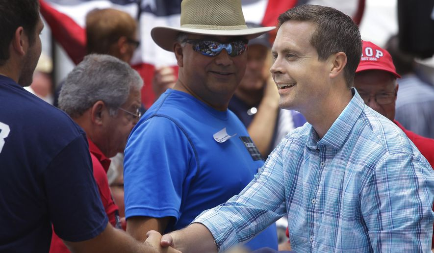 In this Aug. 14, 2014, file photo, U.S. Rep. Rodney Davis shakes hands with people attending the Republican Day rally at the Illinois State Fair in Springfield. (AP Photo/Seth Perlman) ** FILE **