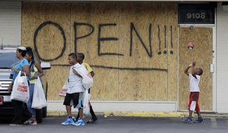 A young boy tosses a football as people walk past a business boarded up to protect against looting in Ferguson, Mo. The unmistakable signs of healing are beginning to dot Ferguson, even the small area of town that has been the center of the world's attention. But those in the community know they've got a long way to go. (Associated Press)