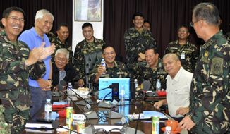 In this photo released by the Armed Forces of the Philippines Public Affairs Office, Philippine Military Chief Gen. Gregorio Catapang, center, reacts after learning about the safe repositioning of Filipino peacekeepers in Golan Heights as they monitor the situation with Philippine Foreign Affairs Secretary Albert Del Rosario, second left, Philippine National Defense Secretary Voltaire Gazmin, third from left seated, at Camp Aguinaldo military headquarters in suburban Quezon city, Philippines on Saturday, Aug. 30, 2014. Catapang said more than 70 Filipino peacekeepers have escaped from two areas in the Golan Heights that came under attack by Syrian rebels. (AP Photo/Armed Forces of the Philippines Public Affairs Office)