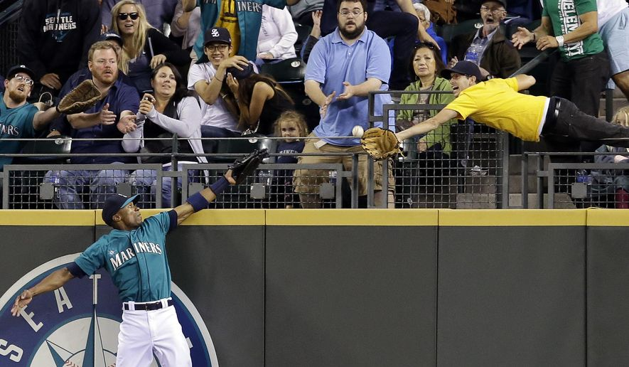 A fan reaches for a home run by Washington Nationals' Bryce Harper as Seattle Mariners center fielder Austin Jackson stretches for it in the eighth inning of a baseball game Friday, Aug. 29, 2014, in Seattle. (AP Photo/Elaine Thompson)