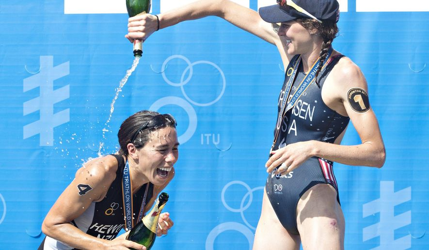 Bronze medalist Andrea Hewitt, left, of New Zealand,  is doused with champagne by gold medalist Gwen Jorgensen, of the United States, after the Elite Women's World Championship Triathlon final in Edmonton, Alberta,  Saturday Aug. 30, 2014. (AP Photo/The Canadian Press, Jason Franson)