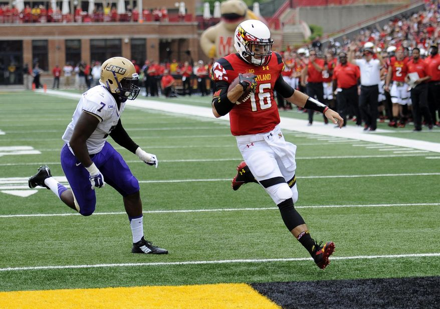 Maryland quarterback C.J. Brown (16) scores a touchdown past James Madison linebacker Rhakeem Stallings (7) during the first half of an NCAA college football game, Saturday, Aug. 30, 2014, in College Park, Md. (AP Photo/Nick Wass)