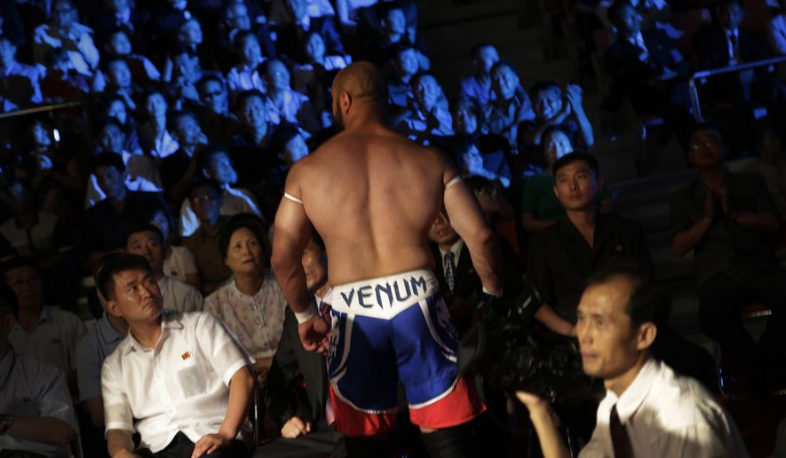 "North Koreans watch a pro-wrestler leave the fighting arena after a match, Saturday, Aug. 30, 2014 in Pyongyang, North Korea. North Koreans got their first look at pro wrestling in about 20-years on Saturday when former NFL lineman Bob ""The Beast"" Sapp, and 20 other fighters from around the world took to the ring for an exhibition in Pyongyang, put together by colourful Japanese pro-wrestler Kanji ""Antonio"" Inoki, who is now a member of parliament. (AP Photo/Wong Maye-E)"