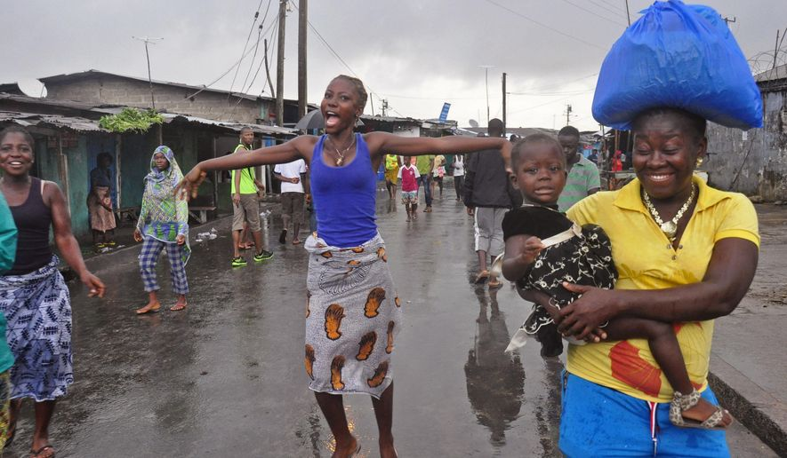 A woman, center,  reacts as she and others celebrate on the streets outside of West Point, that have been closed in by Liberian security forces to stop all movement the past week in a attempt to control the Ebola outbreak in Monrovia, Liberia, Saturday, Aug. 30, 2014. Liberia says it will open up a slum in its capital where thousands of people were barricaded to contain the spread of Ebola. Information Minister Lewis Brown says lifting the quarantine Saturday morning will not mean there is no Ebola in the West Point Slum. (AP Photo/Abbas Dulleh)