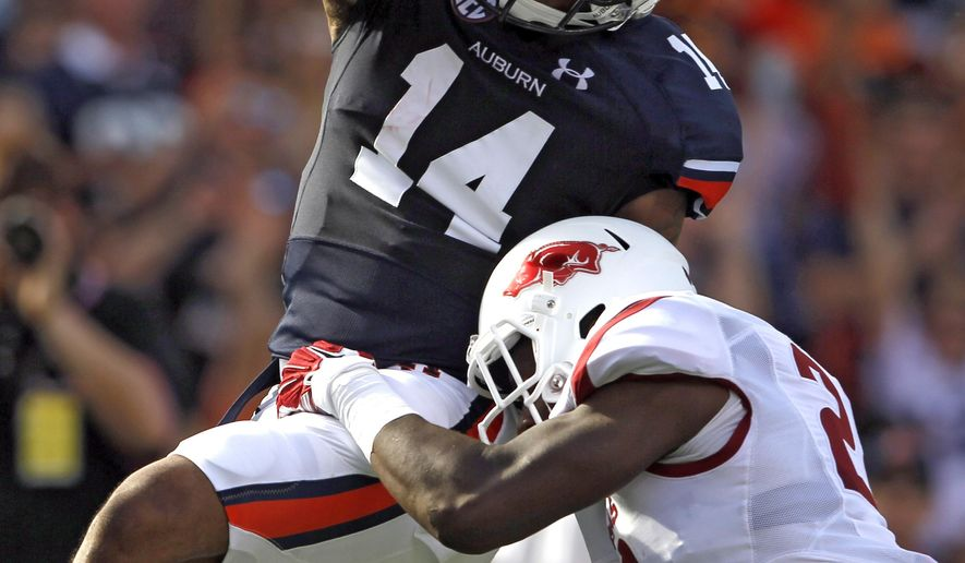 Auburn quarterback Nick Marshall (14) runs in for a touchdown as he is hit by Arkansas safety Josh Liddell (28) during the second half of an NCAA college football game on Saturday, Aug. 30, 2014, in Auburn, Ala. (AP Photo/Butch Dill)