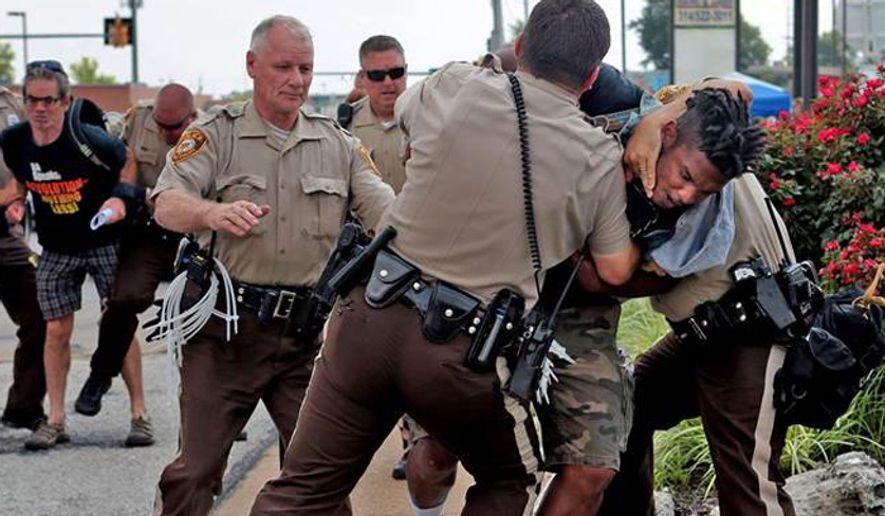 ** FILE ** Police officer Dan Page (left, with zip strips) and fellow cops tackle a man Aug. 18 in Ferguson, Missouri. (Associated Press)