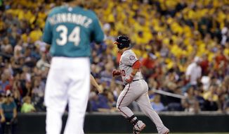 Seattle Mariners starting pitcher Felix Hernandez (34) waits as Washington Nationals' Wilson Ramos rounds the bases on a home run in the fourth inning of a baseball game Friday, Aug. 29, 2014, in Seattle. (AP Photo/Elaine Thompson)