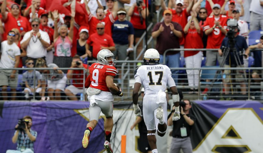 Ohio State wide receiver Devin Smith, left, looks back at Navy cornerback Kwazel Bertrand as he runs in for a touchdown in the second half of an NCAA college football game in Baltimore, Saturday, Aug. 30, 2014. Ohio State won 34-17. (AP Photo/Patrick Semansky)
