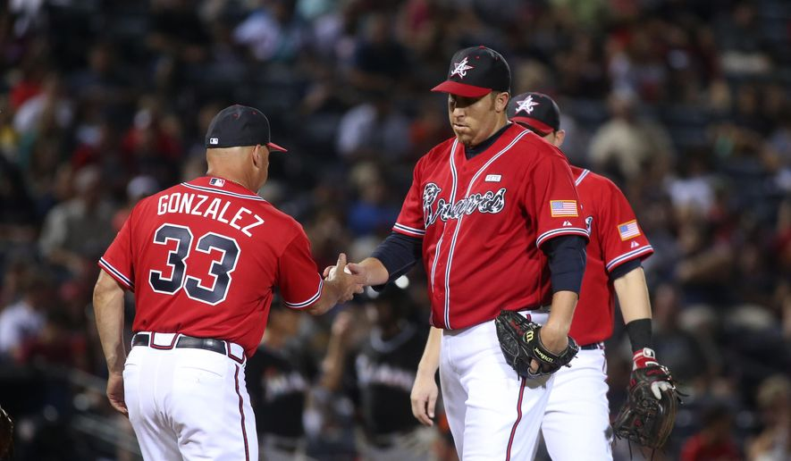 Atlanta Braves manager Fredi Gonzalez (33) removes Atlanta Braves starting pitcher Aaron Harang (34) from the mound in the sixth inning of their baseball game against the Miami Marlins, Saturday, Aug. 30, 2014, in Atlanta. The Marlins won 4-0. (AP Photo/Jason Getz)