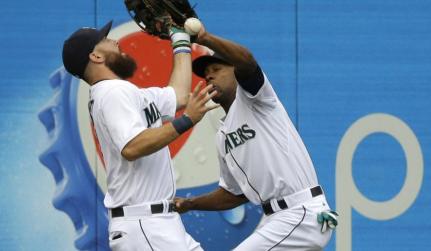 Seattle Mariners center fielder Austin Jackson, right, commits a fielding error as he collides with left fielder Dustin Ackley, left, as they fail to catch a ball hit by Denard Span in the first inning of a baseball game, Saturday, Aug. 30, 2014, in Seattle. (AP Photo/Ted S. Warren)