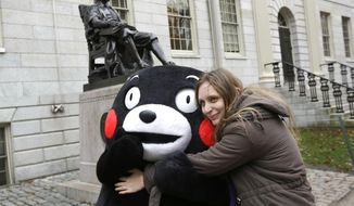 In this Nov. 12, 2013, Kumamon, left, a popular black bear character from Japan, is hugged by Mariel Cerra, of Buenos Aires, Argentina, in front of a statue of John Harvard on the campus of Harvard University in Cambridge, Mass., as the Kumamon character that originated in Japan's Kumamoto prefecture, or state, visited the university and Fenway Park in Boston on the day. (AP Photo/Steven Senne, File)